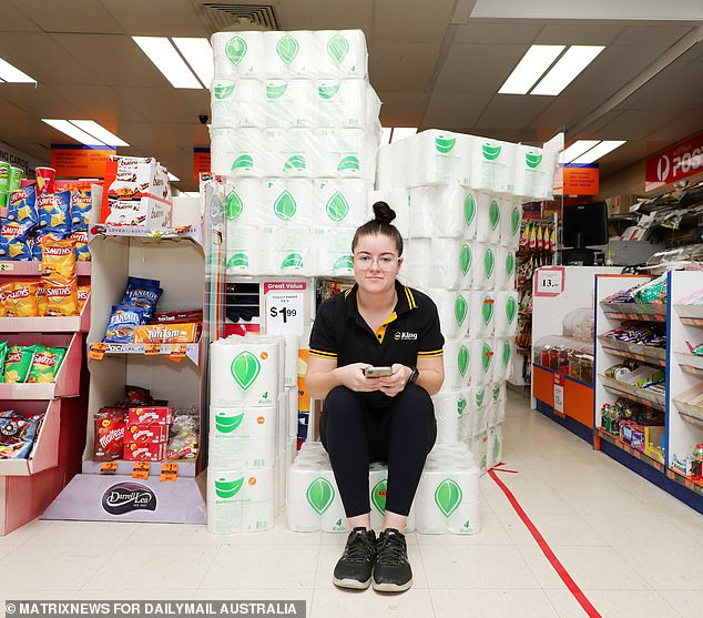 Pictured: One of Ms Deng's shop assistants Roanna James with some of the toilet rolls imported from China by her manager. She said her boss had bought the large quantity of loo roll to help her community to get access to the product at a cheap price