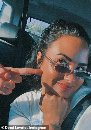 Mwah! Wearing a white T-shirt and narrow sunglasses, Demi kept snapping selfies as she and Max smooched