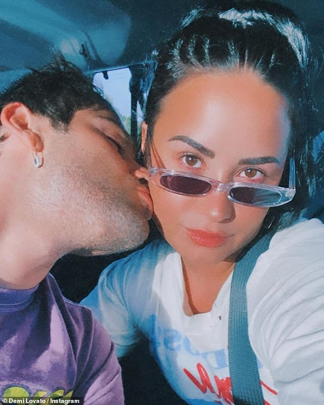 Smoochin': The 27-year-old singer and her beau, 28, larked around as they posed for selfies, with Demi pulling faces for the camera before getting distracted by Max's lips