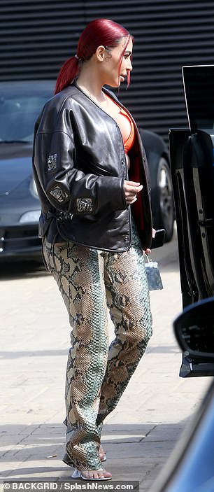Iconic: Kim made sure to stand out with a sexy look wearing snakeskin-print pants, a bold neon bralet and black leather jacket
