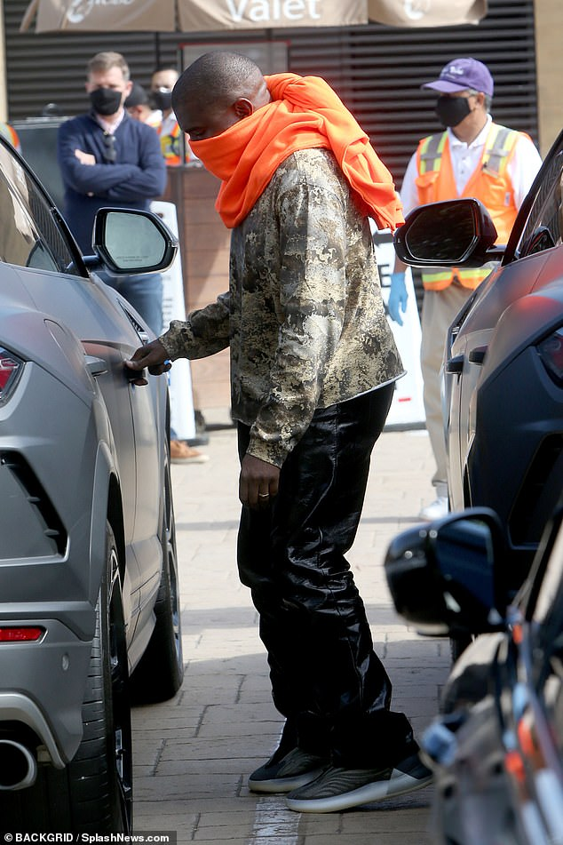 Coordinated: Almost matching his wife, Kanye opted for a camouflage sweater over black pants and covered his nose and mouth with his brightly colored hoodie