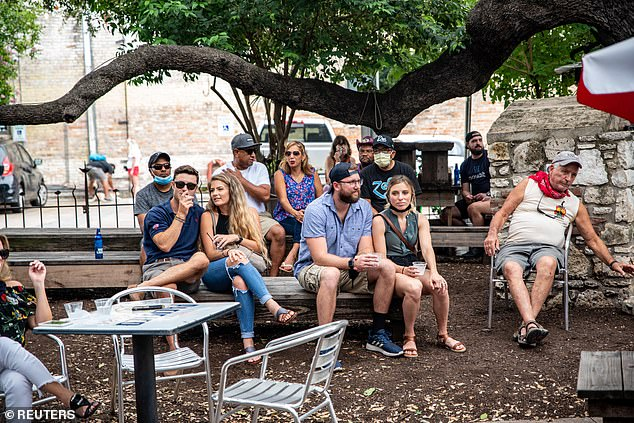 People (pictured on Sunday) sit at an outdoor bar and eating area as cases continue to rise in several states