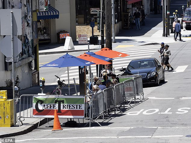 'California had made great progress; they're now unfortunately slipping back and they are changing the rules regarding bars and restaurants,' de Blasio said. Patrons are seen dining outside of a restaurant in San Francisco, California, on June 23