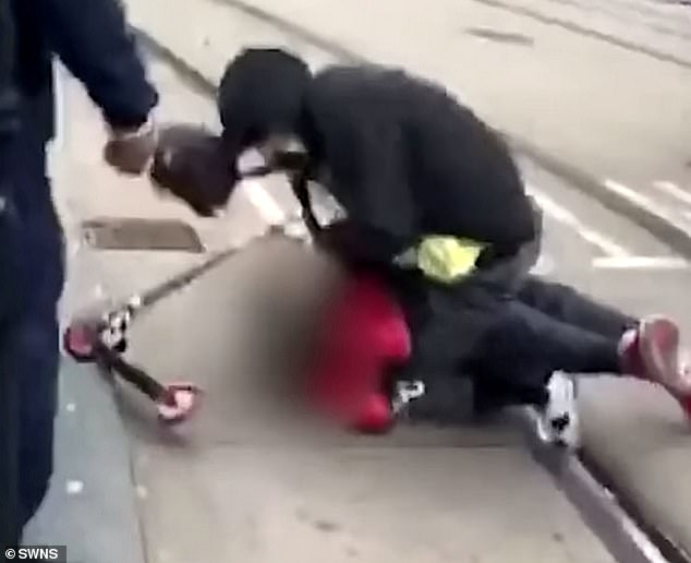 The footage shows the man being repeatedly punched as he curls up in a ball next to a scooter