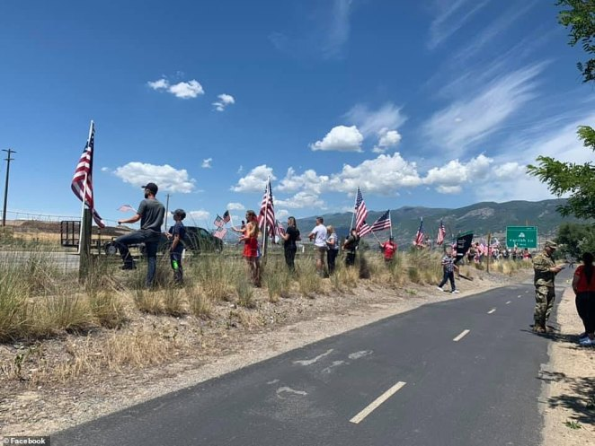 Attendees are seen holding flags as they wait for Allen's hearse to pass by on Friday