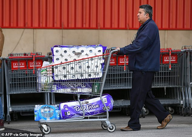 A customer leaves a Melbourne Costco outlet with a trolley full of toilet paper last week. Victoria is battling a surge in coronavirus cases in Melbourne in recent weeks