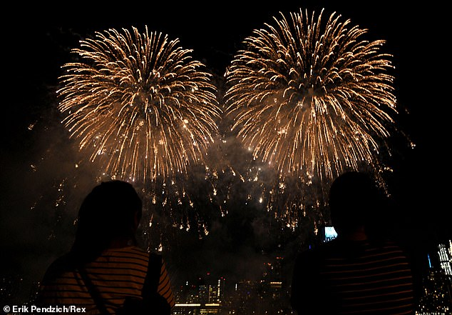 Spectators are pictured watching brilliant plumes of light during the show