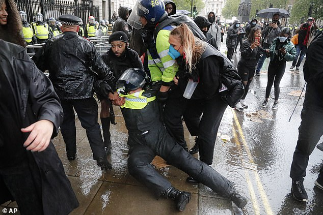 A police officer is injured during scuffles with demonstrators outside Downing Street during a Black Lives Matter march in London on June 6 following the death of George Floyd in the US