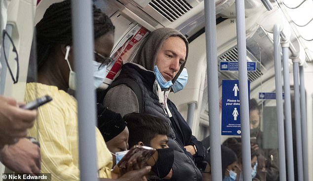 Some commuters wear masks while others have them pulled down below their mouth today