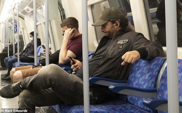 A man looks at his phone while commuting on a Jubilee line service today with no face mask