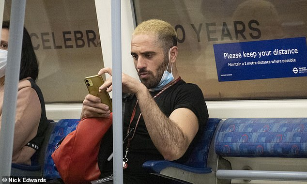 A passenger wears a mask below his mouth on a London Underground train this morning