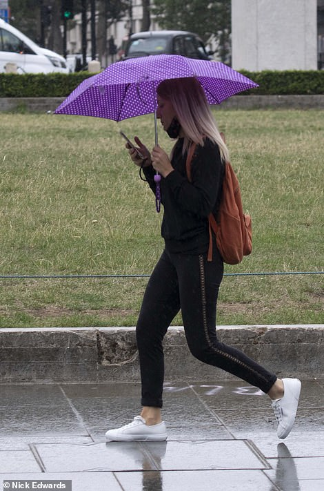 A woman looks at her phone while taking cover from the rain under an umbrella in London today