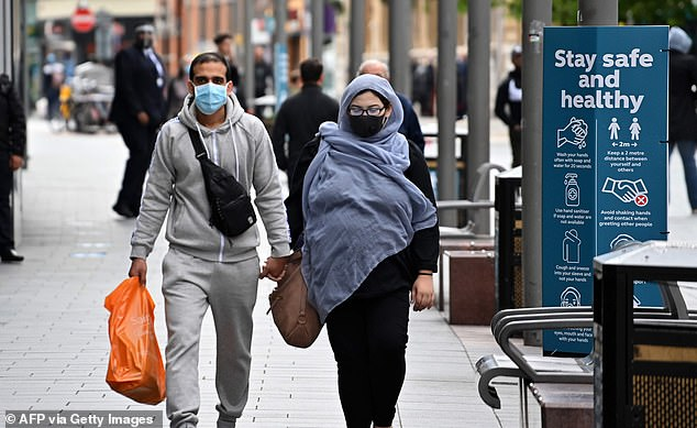 The Government for months refused to advise people to wear face masks but has since made it mandatory for them to be worn on public transport, and recommends them in busy places where social distancing is difficult (Pictured: A couple in Leicester wearing masks)