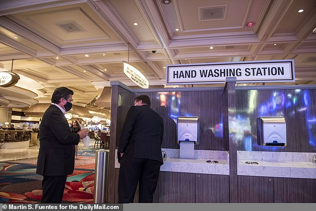 The MGM Grand and Bellagio are operated by MGM Resorts International. In response to the lawsuit, MGM Resorts said the company has offered free testing to workers before returning to the job and requires testing for anyone with symptoms or who might have been exposed (pictured Patrons wash their hands at a designated station inside the Bellagio, June 4)