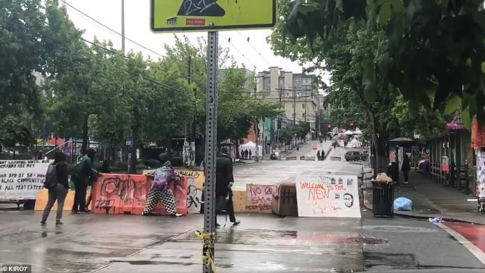 Protesters were then filmed lining up plastic barriers, couches and trash cans in attempt to replace concrete barricade