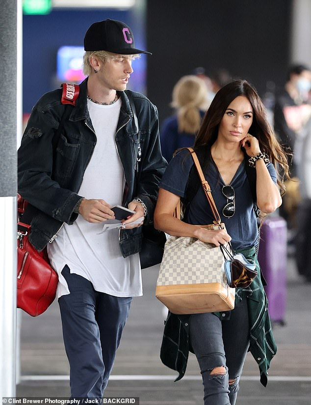 Casual customer: Machine Gun Kelly - real name Colson Baker - donned a denim jacket over plain white T-shirt, and low-top black Vans Old Skool sneakers