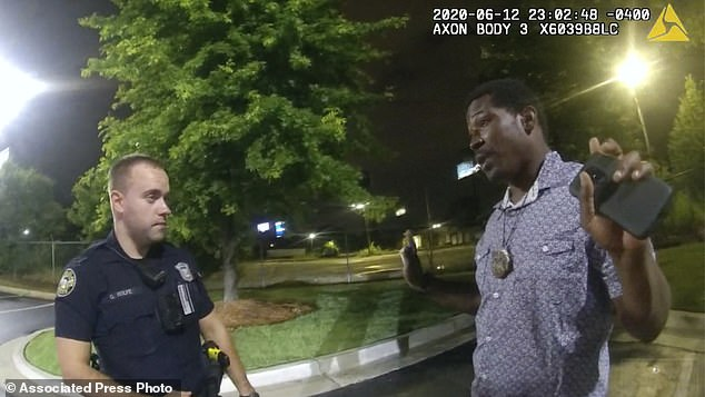This screen grab taken from body camera video provided by the Atlanta Police Department shows Rayshard Brooks speaking with Officer Garrett Rolfe, left, in the parking lot of a Wendy's restaurant on June 12 before he was fatally shot