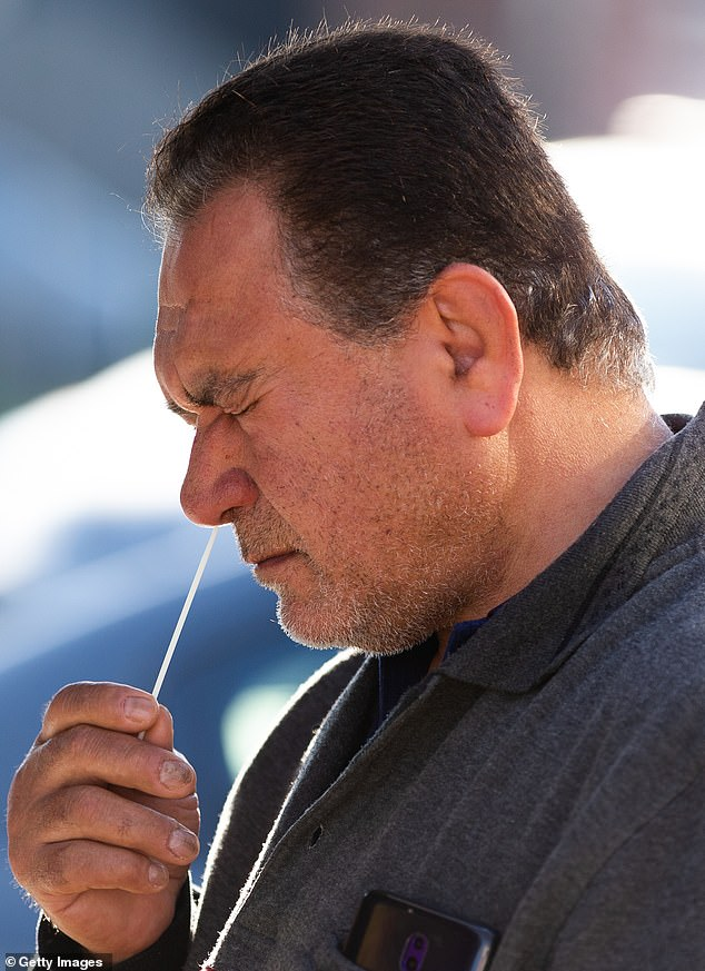 A man places a swab in his nose at a pop-up coronavirus testing facility in Broadmeadows