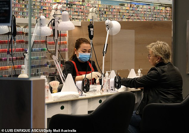 A customer has her nails down at a large shopping centre soon to come under the COVID-19 blanket restrictions
