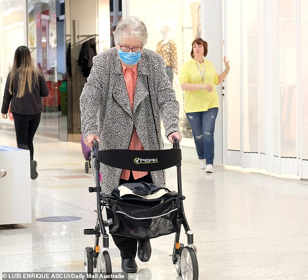 An elderly woman carries out last minute shopping before her suburb goes into lockdown in Melbourne's west