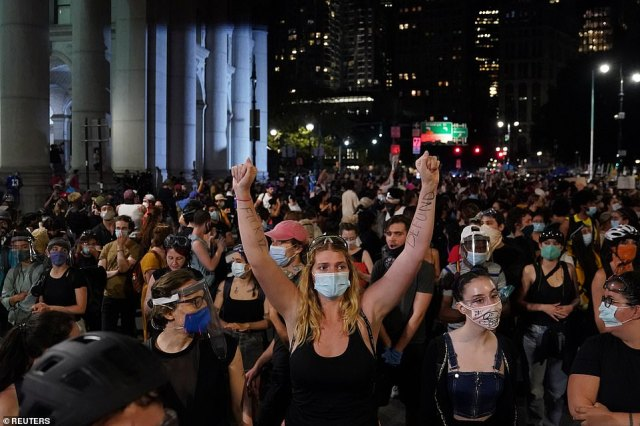 Unrest continues: Protesters chanted slogans during a protest to defund the NYPD in a place they are calling the 'City Hall Autonomous Zone', ahead of Tuesday's vote