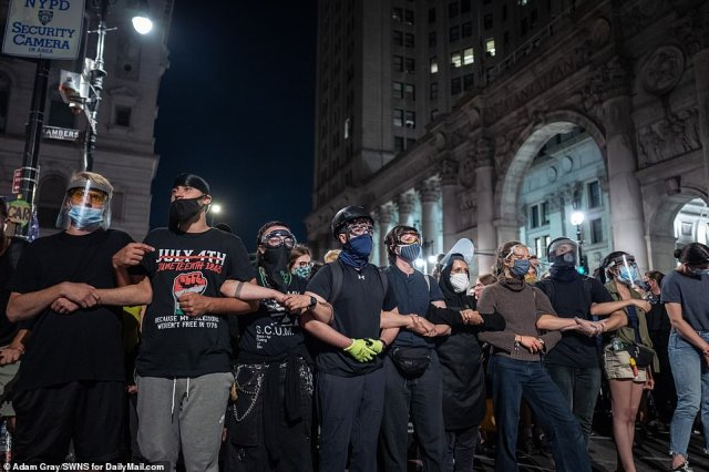 Protesters locked arms outside City Hall on Tuesday as lawmakers debated the city budget on policing amid mounting pressure from its residents