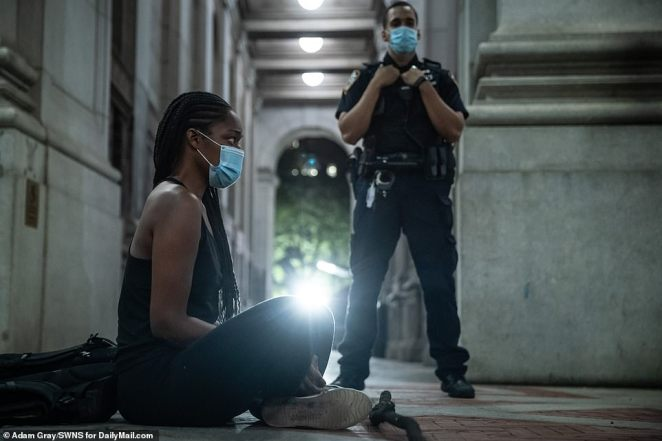 A female protester wearing a protective masks sits near City Hall late Tuesday as a police officer looks on