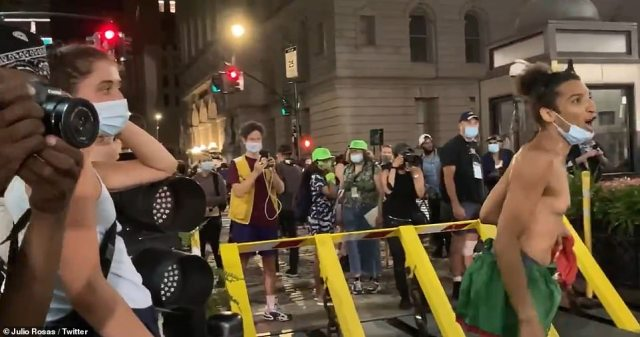 In the video, a woman wearing a face mask (left) begins ridiculing the officers calling them 'f**king idiots' and saying they 'go to clown college' before the other protester joins in