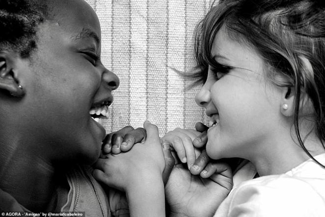 Pictured: Two young girls - one black and one white - hold hands and grin at eachother in a photograph titled 'Amigas' in Spain