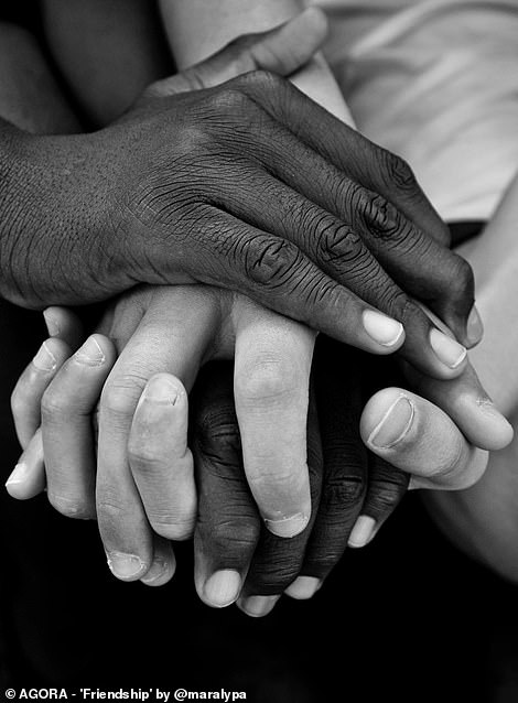 Pictured: Two people - black and white - hold hands in a photograph titled 'friendship'