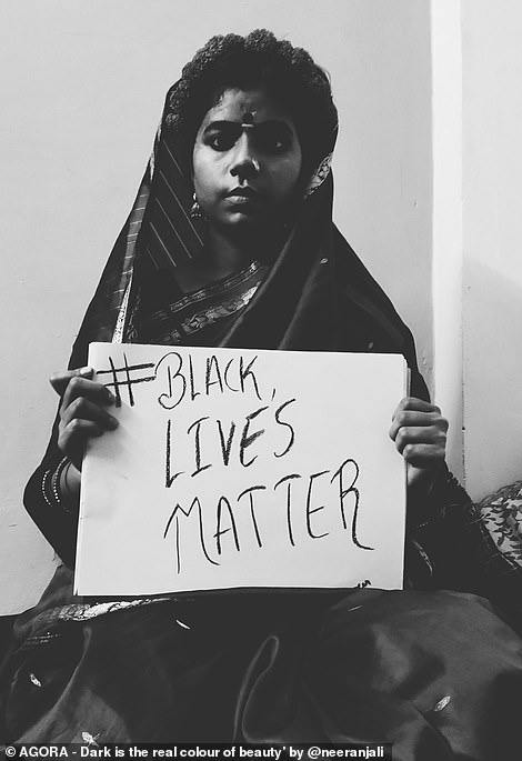 A young woman wearing a traditional Parsi dress holds up a sign that reads 'Black Lives Matter