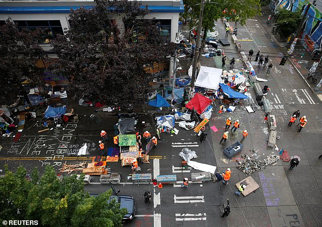 City workers begin to dismantle tents and barricades left behind after the CHOP area in Seattle was reclaimed by police