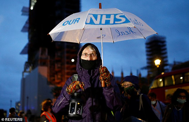 Pictured:  A demonstrator holds an umbrella as NHS staff, unions and campaigners gather for a vigil
