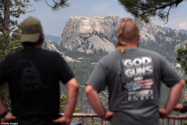 Health experts say the event could lead to a spike in cases, and put not only attendees but also workers at risk. Pictured: Visitors look at Mount Rushmore National Monument, July 2