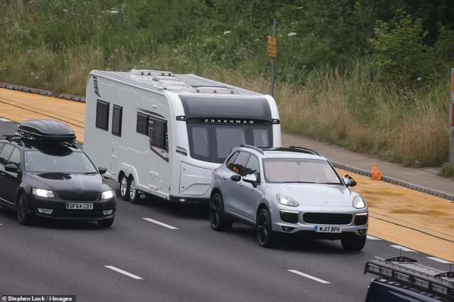 Traffic on the M25 motorway in Kent with one car pictured towing a camper van.Approximately 6.5million Britons are planning overnight stays with friends or family, with around two million driving to campsites