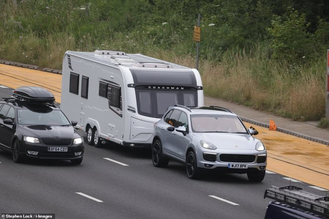 Traffic on the M25 motorway in Kent with one car pictured towing a camper van. Approximately 6.5million Britons are planning overnight stays with friends or family, with around two million driving to campsites