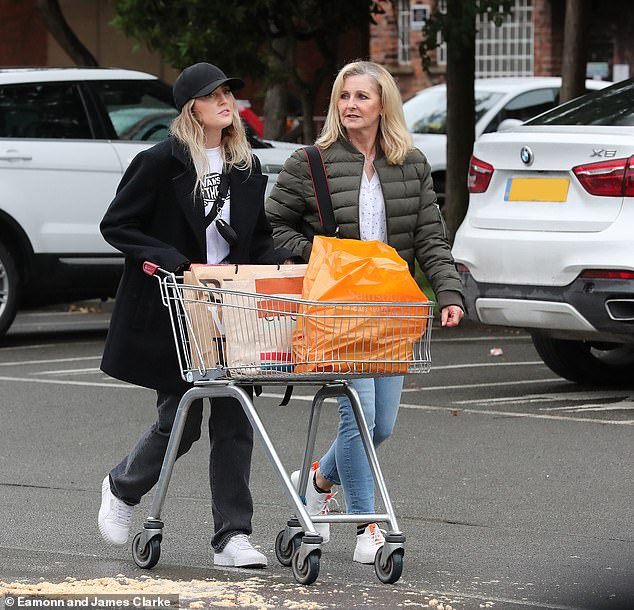 Supermarket race: Little Mix star, 26, dressed in a black wool pea coat and a black sports cap as they braved the rain to stock up on essential items before the weekend