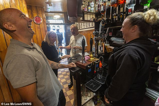 Locals and staff at the Circus Tavern in Manchester share a joke as they reopened today for the first time