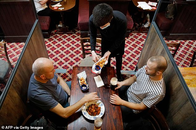 These two pub-goers enjoyed some chicken wings with their drinks at the Goldengrove pub in Stratford in East London today