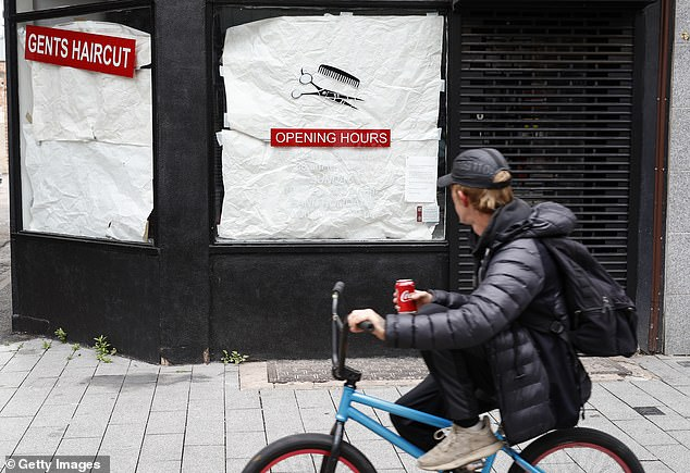 A man cycles past a closed barbers as the area remains under lockdown - unlike the rest of the UK
