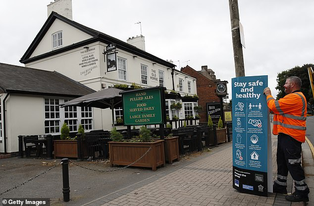 A council worker hangs a social distancing sign on a lamp post outside a closed pub on Saturday