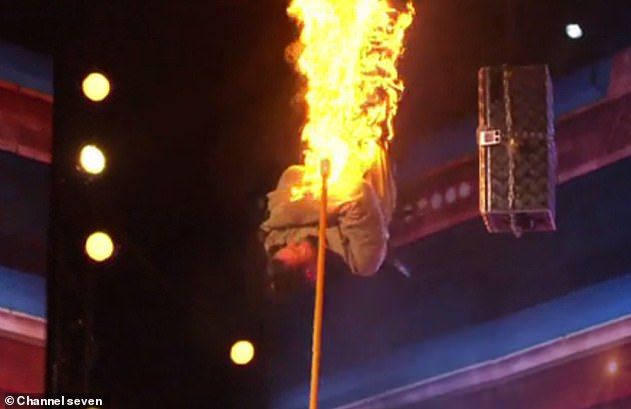 Dangerous! The magician was suspended upside down in a straitjacket above a bed of flaming spikes for the escape stunt (pictured) while on fire