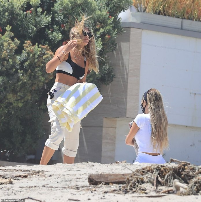 The fight: Sofia's long hair was blown by the wind as she tried to put down her beach towel