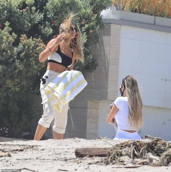 The struggle: Sofia's long hair kept being swept up by the wind as she attempted to lay down her beach towel