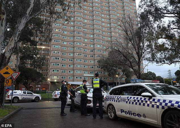 The 'hard lockdown' will see 3,000 people in towers across Flemington, Kensington and North Melbourne forced to stay inside Pictured:Police enforce a lockdown at public housing towers on Racecourse Road in Flemington