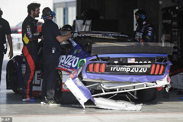 The crew for the car driven by Corey LaJoie looks over the damage to the car after a crash in the pit area during a NASCAR Cup Series auto race at Indianapolis Motor Speedway on Sunday