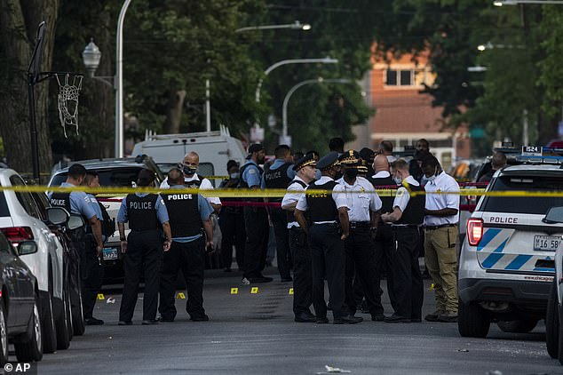 Chicago police officers are seen above in the Austin section of the city where a 7-year-old girl was fatally shot on Friday