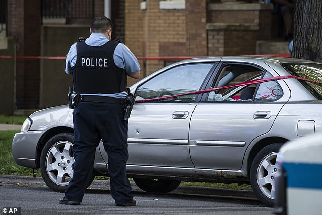 A Chicago police officer investigates the scene of a shooting in Chicago on Sunday