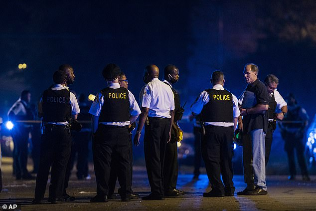 Investigators are seen above in the area of another shooting which took place in the Englewood section of Chicago on Sunday
