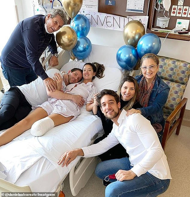 Friends and family members surround Daniella Álvarez at her hospital bed during a visit in June